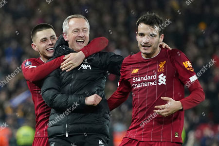 Liverpool's Under 23 coach Neil Critchley, center, celebrates with Liverpool's Pedro Chirivella, right, and Liverpool's Adam Lewis after winning the English FA Cup Fourth Round replay soccer match between Liverpool and Shrewsbury Town at Anfield Stadium, Liverpool, England, . Liverpool won 1-0