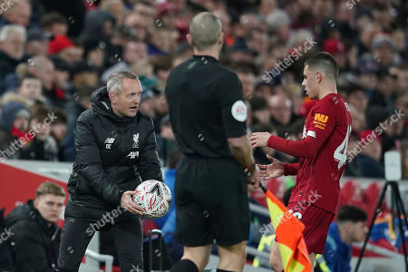 Liverpool's Under 23 coach Neil Critchley, left, passes the ball to Liverpool's Adam Lewis during the English FA Cup Fourth Round replay soccer match between Liverpool and Shrewsbury Town at Anfield Stadium, Liverpool, England