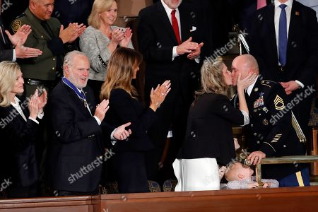 Amy Williams kisses her husband Sgt. 1st Class Townsend Williams after he surprised her by appearing at the State of the Union address by President Donald Trump in a joint session of Congress on Capitol Hill in Washington, . Kathryn and Rush Limbaugh and first Lady Melania Trump watch
