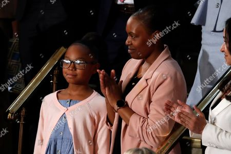 Janiyah, left, and Stephanie Davis of Philadelphia, listen as President Donald Trump delivers his State of the Union address to a joint session of Congress on Capitol Hill in Washington