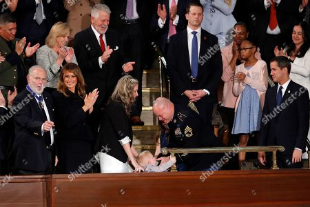 As Amy Williams watches, her husband Sgt. 1st Class Townsend Williams, greets his son Rowan after he surprised them by appearing at the State of the Union address by President Donald Trump in a joint session of Congress on Capitol Hill in Washington, . Rush Limbaugh and first Lady Melania Trump watch