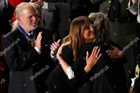 First Lady Melania Trump hugs Amy Williams as Rush Limbaugh watches as President Donald Trump delivers his State of the Union address to a joint session of Congress on Capitol Hill in Washington