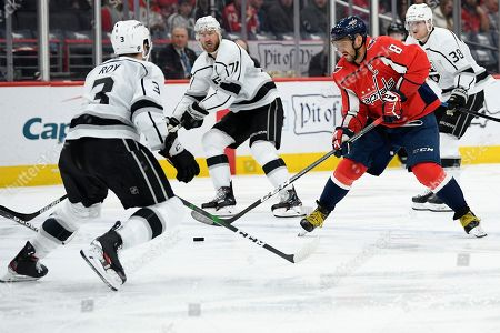 Washington Capitals left wing Alex Ovechkin (8), of Russia, skates with the puck in front of Los Angeles Kings defenseman Matt Roy (3) during the second period of an NHL hockey game, in Washington