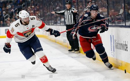 Florida Panthers' Aaron Ekblad, left, and Columbus Blue Jackets' Scott Harrington chase the puck during the second period of an NHL hockey game, in Columbus, Ohio