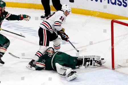 Jonathan Toews, Alex Stalock. Chicago Blackhawks' Jonathan Toews, left, skates over Minnesota Wild's Alex Stalock in the first period of an NHL hockey game, in St. Paul, Minn
