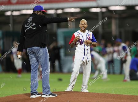 Retired Boston Red Sox player David Ortiz of the Dominican Republic, affectionately known as Big Papi, left, and Puerto Rican singer Ozuna, stand at the pitcher's mound for the opening pitch of the Caribbean Series baseball game between Dominican Republic and Puerto Rico, in San Juan, Puerto Rico