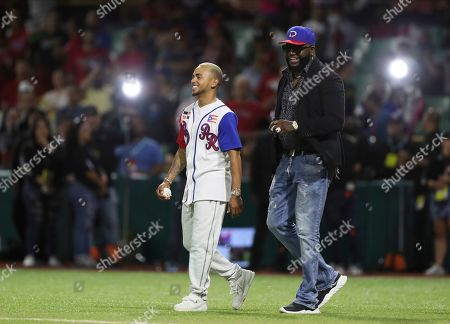 Retired Boston Red Sox player David Ortiz of the Dominican Republic, affectionately known as Big Papi, right, and Puerto Rican singer Ozuna, walk onto the field for the opening pitch of the Caribbean Series baseball game between Dominican Republic and Puerto Rico, in San Juan, Puerto Rico