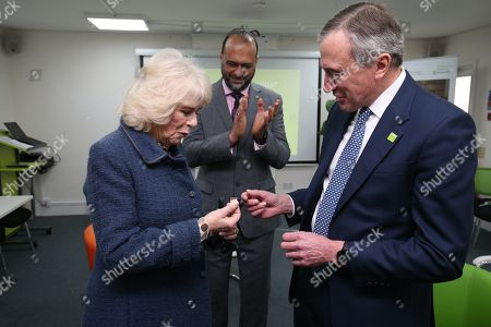 Camilla Duchess of Cornwall receives a badge to mark more than 10 years of service to Bernardo's from chair of trustees John Bartlett (right) and chief executive Javed Khan during a visit to Barnardo's Child and Sexual Abuse and Exploitation Services