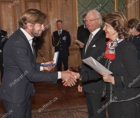 Ruben Ostlund, movie director, receives a medal from King Carl Gustaf and Queen Silvia during a ceremony at the Royal Palace