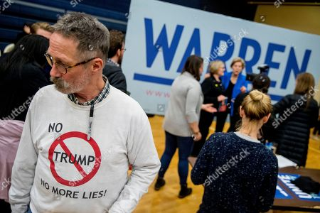 """Elizabeth Warren, Michael Ward. Warren campaign volunteer Michael Ward of Nashua, N.H., wears a shirt that reads """"No Trump No More Lies!"""" as Democratic presidential candidate Sen. Elizabeth Warren, D-Mass., takes photographs with members of the audience at a campaign stop at Nashua Community College, in Nashua, N.H"""
