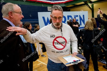 """Bruce Mann, Michael Ward. Warren campaign volunteer Michael Ward of Nashua, N.H., wears a shirt that reads """"No Trump No More Lies!"""" as he speaks to Bruce Mann, left, the husband of Democratic presidential candidate Sen. Elizabeth Warren, D-Mass., at a campaign stop at Nashua Community College, in Nashua, N.H"""
