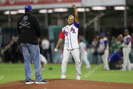 Puerto Rican singer Ozuna, right, jokes with former MLB player David Ortiz of Dominican Republic during the opening pitch at Caribbean Series baseball game between Puerto Rico and Dominican Republic in San Juan, Puerto Rico