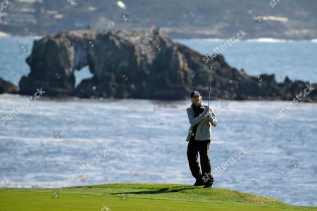 Clint Eastwood follows his shot from off the 18th fairway of the Pebble Beach Golf Links during the celebrity challenge event of the AT&T Pebble Beach National Pro-Am golf tournament, in Pebble Beach, Calif
