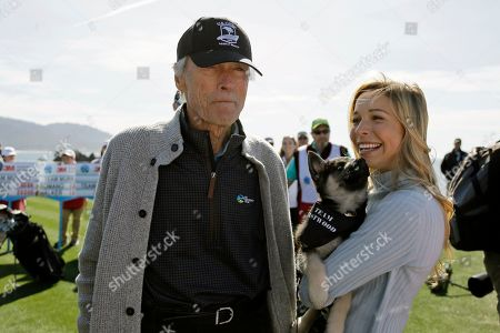 Clint Eastwood, Kira K. Dixon. Clint Eastwood and Kira K. Dixon stand on the 18th green of the Pebble Beach Golf Links and wait to hit during the celebrity challenge event of the AT&T Pebble Beach National Pro-Am golf tournament, in Pebble Beach, Calif