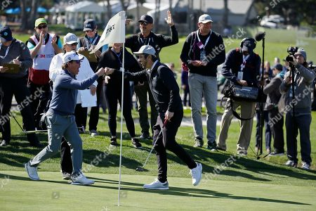 Clay Walker, left, and Ray Romano celebrate on the second green of the Pebble Beach Golf Links during the celebrity challenge event of the AT&T Pebble Beach National Pro-Am golf tournament, in Pebble Beach, Calif