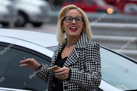 Sen. Kyrsten Sinema, D-Ariz., waves as she departs after the impeachment acquittal of President Donald Trump, on Capitol Hill, in Washington