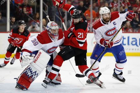 New Jersey Devils right wing Kyle Palmieri (21) keeps his balance in front of Montreal Canadiens goaltender Charlie Lindgren (39) as Canadiens defenseman Shea Weber (6) waits for a pass during the second period of an NHL hockey game, in Newark, N.J