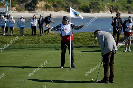 Sir Nick Faldo, center, helps Clint Eastwood with his putt on the 17th green of the Pebble Beach Golf Links during the celebrity challenge event of the AT&T Pebble Beach National Pro-Am golf tournament, in Pebble Beach, Calif