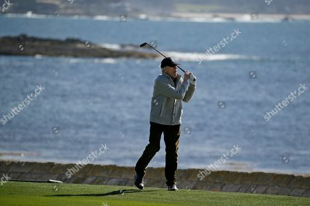 Clint Eastwood follows his approach shot to the 18th green of the Pebble Beach Golf Links during the celebrity challenge event of the AT&T Pebble Beach National Pro-Am golf tournament, in Pebble Beach, Calif