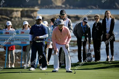 Bill Murray lines up his putt on the 18th green of the Pebble Beach Golf Links during the celebrity challenge event of the AT&T Pebble Beach National Pro-Am golf tournament, in Pebble Beach, Calif. In the background is Alfonso Ribeiro, left, and Nick Faldo, center