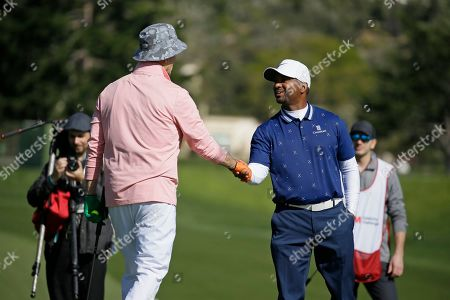 Alfsono Ribeiro, right, greets Bill Murray on the third green of the Pebble Beach Golf Links during the celebrity challenge event of the AT&T Pebble Beach National Pro-Am golf tournament, in Pebble Beach, Calif