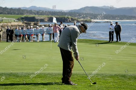 Clint Eastwood begins to chip the ball onto the 18th green of the Pebble Beach Golf Links during the celebrity challenge event of the AT&T Pebble Beach National Pro-Am golf tournament, in Pebble Beach, Calif