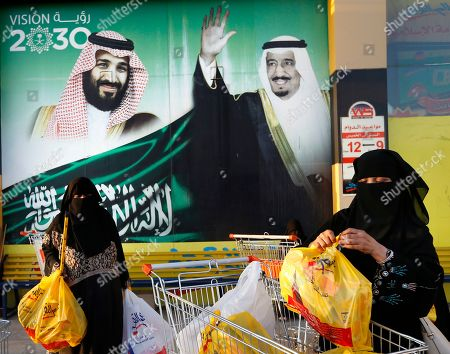 "Women carry their shopping bags past a banner showing Saudi King Salman and his Crown Prince Mohammed bin Salman, left, outside a mall in Jiddah, Saudi Arabia. Human rights organization Amnesty International says Saudi Arabia has used a special anti-terrorism court as ""a weapon of repression"" to imprison peaceful critics, dissidents, activists, journalists, clerics and members of the kingdom's minority Muslim Shiites, including some who were sentenced to death and executed"