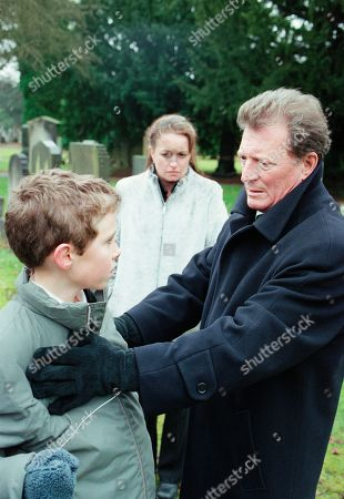 Ep 4987 Friday 16th February 2001 Susan Barlow's funeral takes place with Mike turning up uninvited. Blaming Mike for her death, Ken accuses him of hounding Susan to get Adam, who finds it all too much and runs crying from the graveside. Mike stops him and tells him that he is his father. Adam punches him. With Linda Baldwin, as played by Jacqueline Pirie ; Adam Barlow, as played by Iain De Caestecker ; Mike Baldwin, as played by Johnny Briggs.