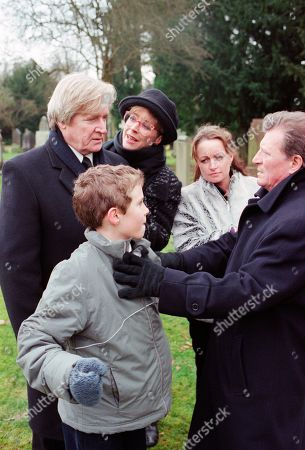 Ep 4987 Friday 16th February 2001 Susan Barlow's funeral takes place with Mike turning up uninvited. Blaming Mike for her death, Ken accuses him of hounding Susan to get Adam, who finds it all too much and runs crying from the graveside. Mike stops him and tells him that he is his father. Adam punches him. With Ken Barlow, as played by William Roache ; Deirdre Rachid, as played by Anne Kirkbride ; Linda Baldwin, as played by Jacqueline Pirie ; Adam Barlow, as played by Iain De Caestecker ; Mike Baldwin, as played by Johnny Briggs.