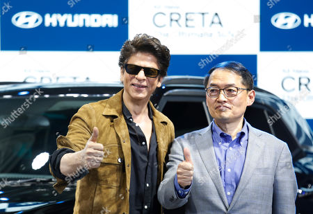 Stock Image of Bollywood actor and brand ambassador of Hyundai Shah Rukh Khan, left, and Hyundai MD and CEO S.S. Kim display the thumbs up at the launch of the all new Creta car during the Auto Expo, in Greater Noida near New Delhi, India