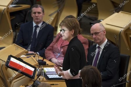 Scottish Parliament First Minister's Questions - reflected sunlight shines on the face of Nicola Sturgeon, First Minister of Scotland and Leader of the Scottish National Party (SNP), during FMQs. Also pictured are Michael Matheson, Cabinet Secretary for Transport, Infrastructure and Connectivity, and and John Swinney, Deputy First Minister and Cabinet Secretary for Education and Skills.