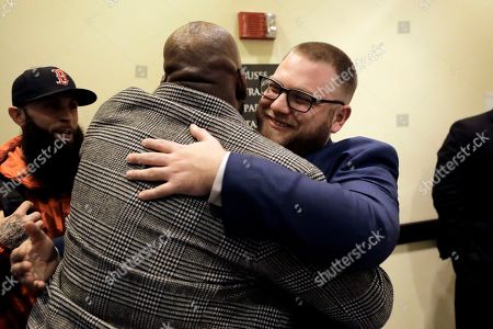 Kevin Hart, Mike Whittaker. Entrepreneur Kevin Hart, of Randolph, Mass., center left, receives a hug from Mike Whittaker, right, director of operations at Pure Oasis, after attending a meeting of the Massachusetts Cannabis Control Commission, in Worcester, Mass. The commission voted in favor of final approval for licenses for a number of cannabis shops in the state, including Pure Oasis, a soon-to-open pot shop in Boston's Dorchester neighborhood