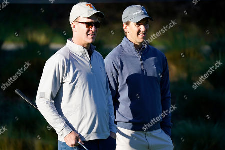 Peyton Manning, left, and his brother Eli Manning wait to hit from the first tee of the Spyglass Hill Golf Course during the first round of the AT&T Pebble Beach National Pro-Am golf tournament, in Pebble Beach, Calif