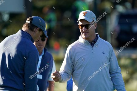 Peyton Manning, right, and Eli Manning prepare to hit from the first tee of the Spyglass Hill Golf Course during the first round of the AT&T Pebble Beach National Pro-Am golf tournament, in Pebble Beach, Calif
