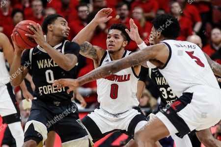 Wake Forest guard Brandon Childress (0) looks to pass as he's pressured by Louisville guard Lamarr Kimble (0) and forward Malik Williams (5) during the second half of an NCAA college basketball game, in Louisville, Ky. Louisville won 86-76