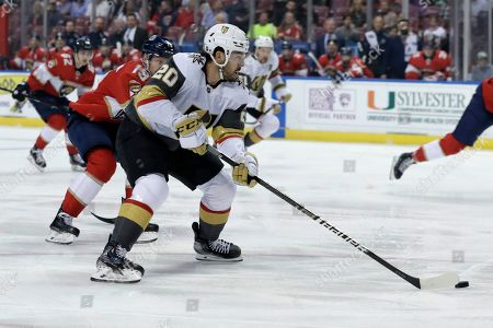 Stock Photo of Chandler Stephenson, Mike Matheson. Vegas Golden Knights center Chandler Stephenson (20) skates with the puck as Florida Panthers defenseman Mike Matheson (19) pursues during the first period of an NHL hockey game, in Sunrise, Fla
