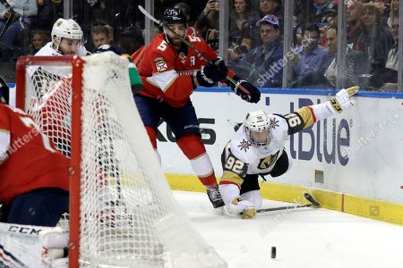 Tomas Nosek, Aaron Ekblad. Vegas Golden Knights left wing Tomas Nosek (92) falls to the ice as Florida Panthers defenseman Aaron Ekblad (5) defends during the first period of an NHL hockey game, in Sunrise, Fla