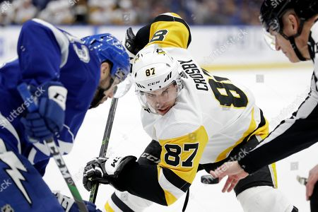 Sidney Crosby, Cedric Paquette, Brian Murphy. Pittsburgh Penguins center Sidney Crosby (87) faces off against Tampa Bay Lightning center Cedric Paquette (13) during the first period of an NHL hockey game, in Tampa, Fla. Dropping the puck is linesman Brian Murphy