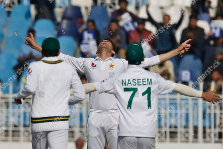 Pakistan pacer Shaheen Shah Afridi, center, celebrates with teammates after taking the wicket of Bangladesh batsman Mahmudullah during the first day of their 1st test cricket match at Rawalpindi cricket stadium in Rawalpindi, Pakistan