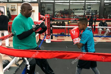 """James """"Buster"""" Douglas, the former world heavyweight champion, works with a student at the Thompson Community Center in Columbus, Ohio, where he teaches youth boxing. In one of the more spectacular upsets in sports history, Douglas defeated Mike Tyson, the reigning world heavyweight champion on Feb. 11, 1990, in Tokyo"""
