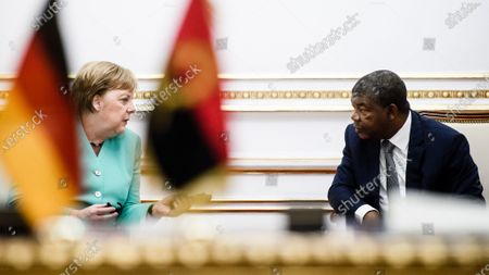 German Chancellor Angela Merkel (L) and Angola's President Joao Lourenco talk behind German and Angolan flags during a contract signing ceremony for the german academic exchange service (DAAD) government scholarship programme and an air transport agreement at the presidential palace in Luanda, Angola, 07 February 2020. Merkel is on a three-day trip to South Africa and Angola.