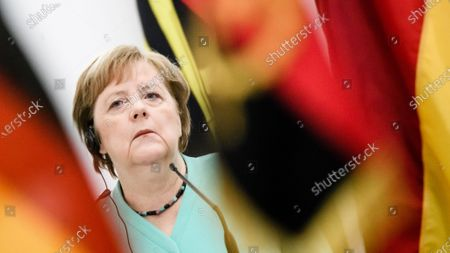 German Chancellor Angela Merkel listens to the translation with an in ear piece during a joint press conference with Angola's President Joao Lourenco (not in the picture) at the presidential palace in Luanda, Angola, 07 February 2020. Merkel is on a three-day trip to South Africa and Angola.