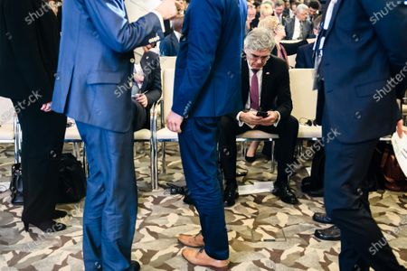 Stock Photo of Siemens CEO Joe Kaeser looks on his phone prior to the beginning of a German-Angolan economy forum in Luanda, Angola, 07 February 2020. Merkel is on a three-day trip to South Africa and Angola.