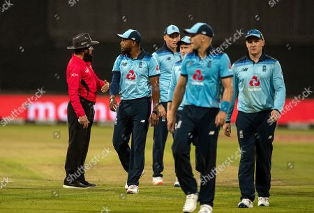 Umpire Aleem Dar of Pakistan, far left, gestures to the England players to leave the field as plays is suspended due to rain during the 2nd One Day International cricket match between South Africa and England at Kingsmead stadium in Durban, South Africa