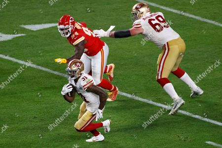 Stock Image of San Francisco 49ers running back Raheem Mostert (31) rushes past Kansas City Chiefs outside linebacker Terrell Suggs (94) during the NFL Super Bowl 54 football game, in Miami Gardens, Fla