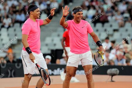 Trevor Noah and Rafael Nadal high five after winning a point against Roger Federer and Bill Gate in the exhibition match held at the Cape Town Stadium in Cape Town, South Africa