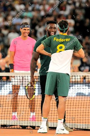 Springbok Captain Siya Kolisi, center, presents Roger Federer with his own Springbok rugby jersey while Rafael Nadal looks on ahead of their exhibition tennis match held at the Cape Town Stadium in Cape Town, South Africa