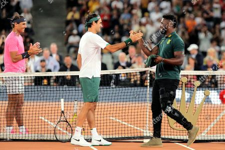 Springbok Captain Siya Kolisi, right, greets Roger Federer, center, while Rafael Nadal looks, on ahead of their exhibition tennis match held at the Cape Town Stadium in Cape Town, South Africa