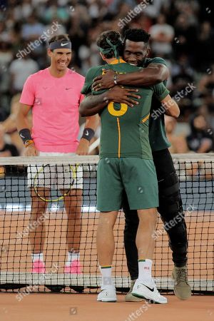Springbok Captain Siya Kolisi, right, hugs Roger Federer after presenting him with a Springbok rugby jersey while Rafael Nadal looks on ahead of their exhibition tennis match held at the Cape Town Stadium in Cape Town, South Africa