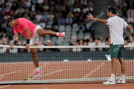 Rafael Nadal, left, jumps the net while Roger Federer watches on during their exhibition tennis match held at the Cape Town Stadium in Cape Town, South Africa